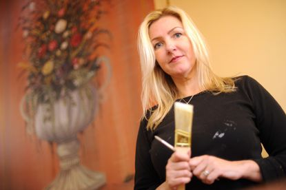 """Mary Veiga, a """"faux painter,"""" decorates the wall of a client's house in Marriottsville."""