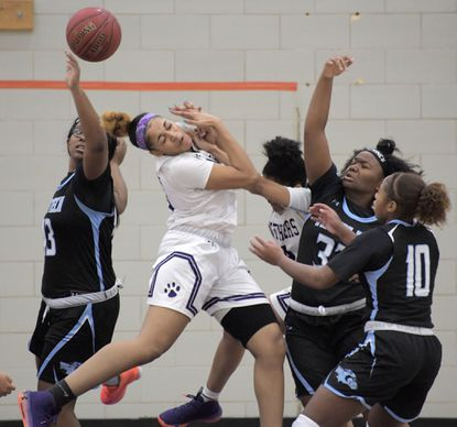 Western Tech Wolverines' Troi Williams (arm raised, right) and Sydney Stokes (10) defend as Pikesville Panthers forward Charia Roberts gets hit by her own teammate, guard Tyra Robinson (right) while battling Maya Britton (left) for a rebound Fri., Dec. 13, 2019. (Karl Merton Ferron/Baltimore Sun Staff)