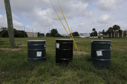 """Barrels identified by stickers as IDW, or """"investigation derived waste,"""" full of soil and water sit in a field designated by the EPA as an intensely polluted Superfund site called Anodyne North Miami Beach on Sept. 6, 2017."""
