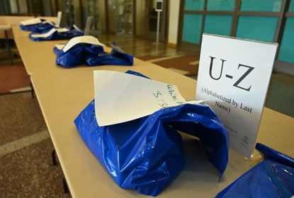 Reserved library materials are placed on tables, designated by customer's names and pickup times, at the MIller Branch as the Howard County Library System began their contactless pickup of library materials on Monday, June 29. The system relies on plastic bags.