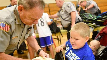 Westminster Police Chief Jeff Spaulding helps Noah Howard, 5, pick out school supplies during the 2nd Annual Shop with a Cop Back to School Kickoff at Westminster West Middle School Tuesday, August 15, 2017.