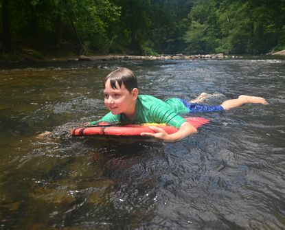 Timothy Tritt finds a fun spot to play on his board as he and his family stay cool and have some fun playing in the cool waters of Deer Creek in Rocks State Park Wednesday June 30, 2021 as temperatures climbing into the upper 90's in Harford County.