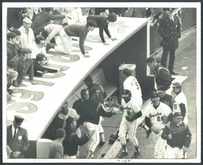 Teammates and fans welcome hero Brooks Robinson (5) as he heads for the dugout after lining the game-winning hit to right center on April 11, 1970. (William Hotz/Baltimore Sun)