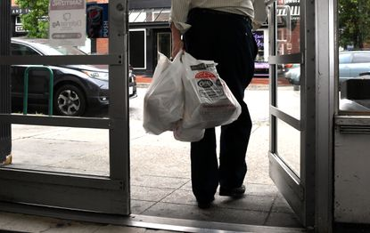 A customer leaves with plastic bags of groceries at Eddie's Market in Mount Vernon on Sept. 22, 2021. That practice of shopping with single-use plastic bags officially ends in Baltimore on Friday, Oct. 1. (Barbara Haddock Taylor/Baltimore Sun).