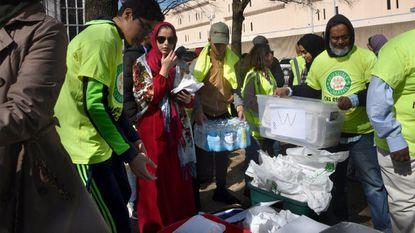 Volunteers take time out from Muslim convention to distribute food to needy