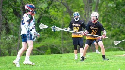 Gamber boys lacrosse players Mikey Simons (30) and Andrew Grandinetti (99) play defense during a recent game.