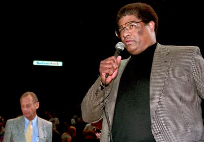 Washington Bullets head coach Wes Unseld announces to the fans that he has coached his last basketball game for the Bullets as Bullets owner Abe Pollin stands nearby after their game against the Charlotte Hornets in Landover, Md., Sunday April 24, 1994. (AP Photo/Ted Mathias)