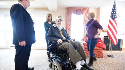 Ken Dolan tests his wheelchair after receiving it through Friends of Disabled American Veterans in Carroll County on Feb. 1. Bill Murphy, left, the organization's co-founder, is joined by Pam McGlynn and Lisa Powers, daughters of Wayne Pool, who originally owned the wheelchair.