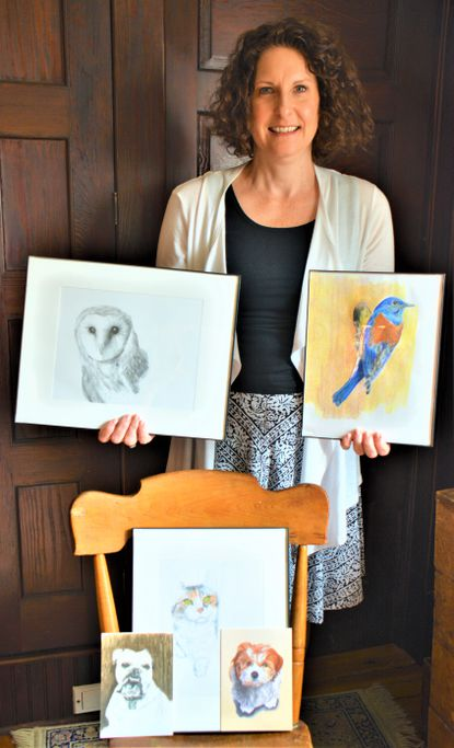 Molly Kuehner is pictured with her pencil drawings of dogs and a bird.