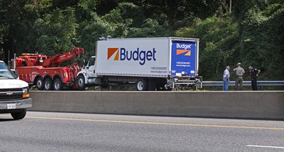 A rental box truck is readied to be towed away from the inner loop of the Baltimore Beltway in September. Maryland law requires passing vehicles to either move over a lane or slow down when approaching an emergency vehicle with lights flashing such as a tow truck.