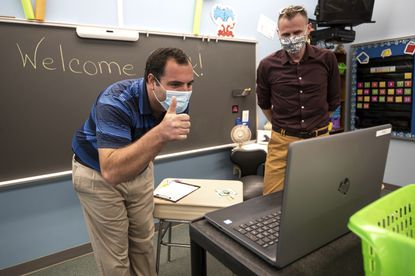 Valley View School District superintendent Dr. Michael Boccella, left, gives a thumbs-up to students learning virtually with first grade teacher Chris Olson on the first day of school at Valley View Elementary School in Blakely, Pennsylvania on Thursday, August 27.