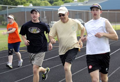 Twins Mark Worley (right) and Bruce Worley (left) train for the Special Olympics with their father, John Worley, at Oakland Mills High School.