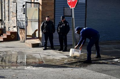 Baltimore police wash blood off the street on the scene of a double homicide. The city reached the grisly milestone of 300 homicides for the fifth year in a row earlier this month.