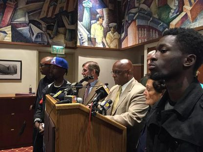 Self-described gang members stand with members of the City Council to condemn rioting