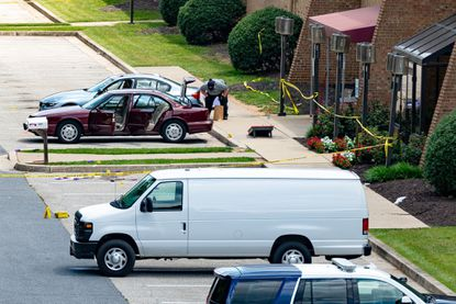 """Law enforcement personnel investigate the scene of a shooting that occurred """"within feet"""" of the Daltile building on Progress Way in Eldersburg."""