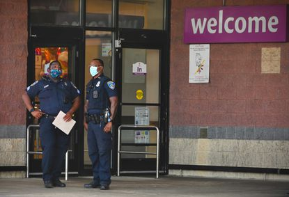 Baltimore Police officers investigate a crime scene at the Giant in Reisterstown Plaza where a grocery store armed security guard shot two people inside, killing one of them, after an altercation late Tuesday afternoon, July 13. (Ulysses Muñoz/Baltimore Sun). .
