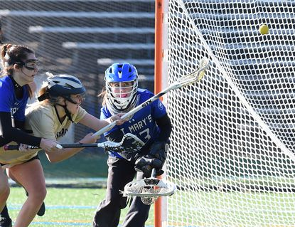 John Carroll's Lydia Ward, center, battles St. Mary's Delaney Brimhall, left, and goalie Madigan Brewer as they go for the loose ball in front of the St. Mary's goal during the girls lacrosse game at John Carroll Friday, March 19, 2021.