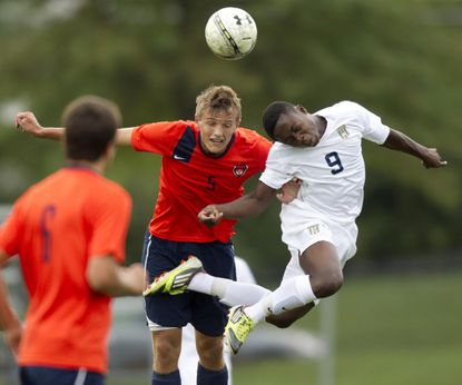 Reservoir's Kyle Saunderson, left, and River Hill's Mike Faderin, right, go up for a header during the boys soccer game.
