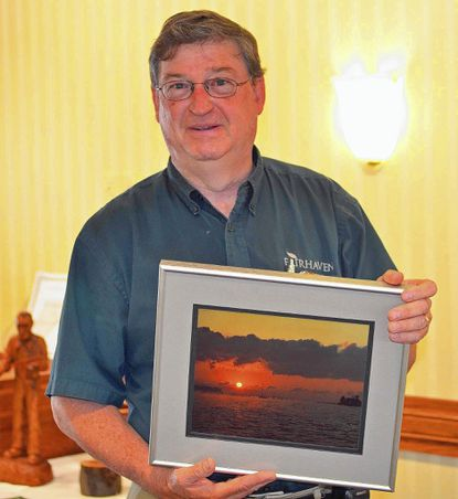 Dave Taylor holds his photograph of sunrise over the Magothy River, near Annapolis. Taylor, who has worked for Fairhaven for more than 30 years, is showing this photograph in the retirement community's employee and resident art exhibit. The exhibit closes Aug. 27.