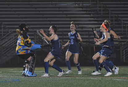 Howard field hockey players run to their keeper Rachel Murphy to celebrate their penalty strokes victory at Marriotts Ridge High School on March 31.