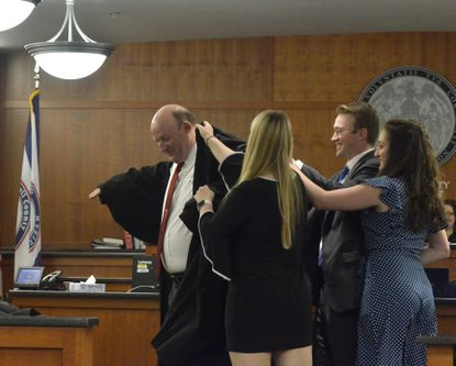 Judge Richard Titus's family, his daughter Emily Titus, son Drew Titus and fiance Miranda Kotidis, and Titus's wife Marlene (obscured) help him into his judicial robes on Dec. 2 at his investiture on the Carroll County Circuit Court.