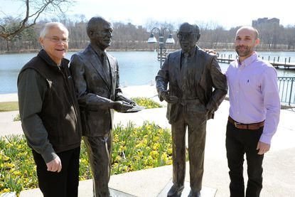 Ned Tillman, left, and Sean Harbaugh, who will lead a walking tour on March 26, visit statues of Columbia founder James Rouse, right, and his brother, Willard Rouse, at the downtown lakefront.