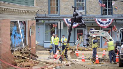 The Phoenix Emporium, left, shows wall damage while repair crews work on Main Street at Maryland Avenue after the second devastating flash flood that swept through the historic center.