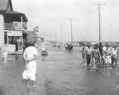 """Mountainous waves swept into the resort and covered some of the streets with two feet of sand. Water was still ankle-deep at the time of this photo. Described in the American Meteorological Society's August 1933 weather review as """"one of the most severe storms that has ever visited the Middle Atlantic Coast,"""" the slow-moving weather mass dumped 10 inches of rain a day for nearly a week, even before wind gusts as high as 80 mph and a 7-foot tide arrived."""