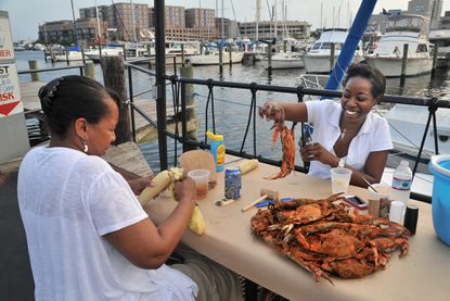 Two women enjoy crabs and corn at Captain James Landing, the Canton crab house with a waterfront outdoor deck.