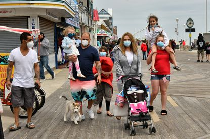 Chris, carrying his youngest daughter, and wife Heather Ruth Haddix, pushing stroller, stroll along the boardwalk with their five children. The Dundalk family welcomed the break from sheltering at home. Moderate crowds returned to Ocean City this weekend after Gov. Larry Hogan lifted the stay-at-home order. Signs urged visitors to wear masks and maintain social distance. May 17, 2020