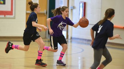 Kira Balis, left, chases after ball handler Amelia Fudalla during a Catonsville 11-12 girls basketball game at Catonsville Middle School on Jan. 27. Members of Catonsville's rec basketball teams purchased pink socks to raise funds the American Cancer Society.
