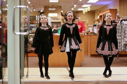 """Teelin Irish Dance Company and sisters, from left, Piper, 7, Lucy, 10, and Madison Laudeman, 13, all of Baltimore County, perform """"Jump"""" in the front doorway of the store, Kashmir, at Shops at Kenilworth in Towson, on March 3. Members of the dance company, which is run by Towson University graduate Maureen Gately, will perform this Sunday, March 11, at Baltimore's annual St. Patrick's Day Parade. Pat McCarty and her husband, Javid Mahajan, from Kashmir, India, owners of Kashmir, said they opened the shop in July and wanted to host an event to celebrate the area's diverse culture."""