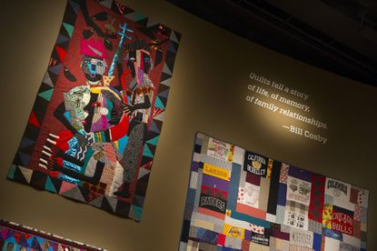 In this Nov. 6, 2014, photo, quilts from the Bill and Camille Cosby collection hang at the Smithsonian's National Museum of African Art in Washington. The Smithsonian Institution stands firmly behind an exhibition showcasing Bill Cosby's private art collection, even as many other major institutions have distanced themselves from the comedian following unfolding sexual assault allegations against him.