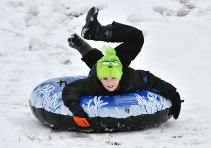 Noah Vogel, 8, of Eldersburg, zips down the slope at Carrolltowne Elementary School in Sykesville last month. The rise of on-line instruction has raised questions about whether school should ever be cancelled by weather in the future. (Amy Davis/Baltimore Sun).