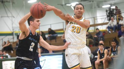McDaniel's Braden Caldwell, right, dishes the ball to a teammate as Joey Kern of Johns Hopkins gives chase during a mens basketball game at McDaniel College on Wednesday, Jan. 30.