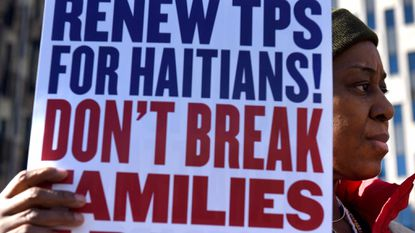 "Immigrant advocates rally against ""DHS decision to terminate TPS for Haitians"" during a rally in New York."