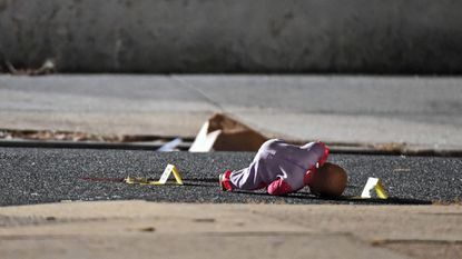 Amy Hayes' doll is shown next to police shooting tags as Baltimore City Police officers investigate the scene of a shooting last week at the 1000 block of McKean Ave.