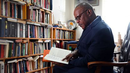 Rev. Dr. Alvin C. Hathaway, Sr., senior pastor of Union Baptist Church, reads books in his home office. He recently used a $40,000 grant to find out what Baltimore residents think about using a surveillance plane to fight crime.