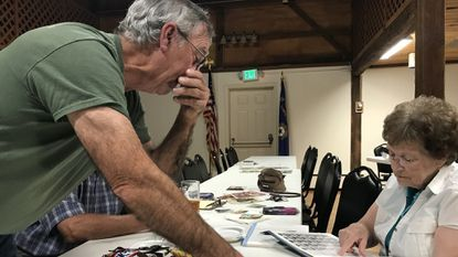 James Moore III looks over his military yearbook and talks with Elinore Frush in American Legion Post 200 in Hampstead. Moore and Alan Grieger discussed their lifelong friendship at the Legion, recounting their time in the Boy Scouts, the Vietnam War and in business together.