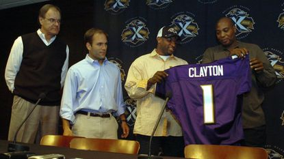 Ravens coach Brian Billick, left, and director of college scouting Eric DeCosta, second from left, watch as general manager Ozzie Newsome, right, gives No. 1 draft pick Mark Clayton his jersey at a news conference April 24, 2005. DeCosta succeeded Newsome as GM last month.