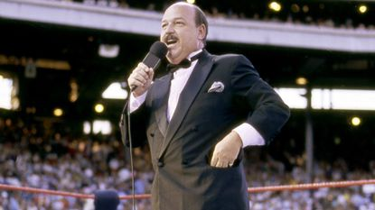 """In this July 31, 1988 photo provided by the WWE, """"Mean"""" Gene Okerlund addresses the crowd before a pro wrestling event in Milwaukee. Okerlund, who interviewed pro wrestling superstars """"Macho Man"""" Randy Savage, The Ultimate Warrior and Hulk Hogan, has died. He was 76."""