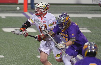 Maryland's Austin Henningsen beats Albany Great Danes' Zack Ornstein at the face off during men's college lacrosse in College Park.