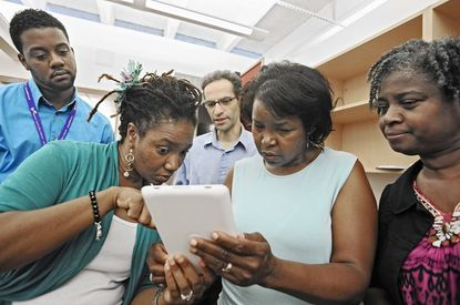 Nyilah Covington, second left, a librarian at the Pennsylvania branch of the Enoch Pratt Free Library, helps train the staff at the Reisterstown branch (l-r) librarian assistant Lamar Pinkett, librarian Greg Fromme, branch manager Vera Fattah and office supervisor Jacqueline Linton on the use of a Nook computers.