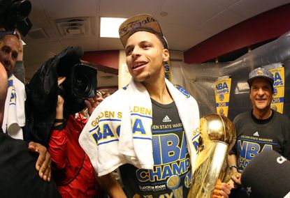Stephen Curry, #30 of the Golden State Warriors, celebrates with the Larry O'Brien NBA Championship Trophy in the locker room after they defeated the Cleveland Cavaliers in Game Six of the 2015 NBA Finals.