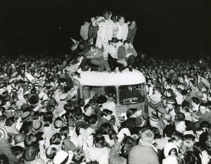 An estimated 30,000 fans mob the Baltimore Colts on Sunday, Dec. 28, 1958 after their return to Friendship Airport from a National Football League championship victory. It was the first overtime in the championship, with the Colts defeating the New York Giants 23-17 at Yankee Stadium.