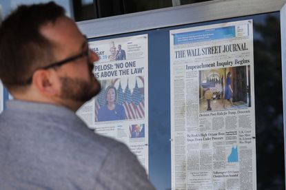 A man stops to look at newspaper front pages, from around the United States, on display at the Newseum in Washington, Wednesday, Sept. 25, 2019.