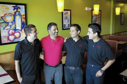 Columbia resident Series Peeyush, left, co-owner of Bella Indian/Italian restaurant in Laurel, is originally from Nepal. Other restaurant staff include manager Mohan Dhakal, also from Nepal, and Bijaya Dhakal and Kushal Dhakal, who all live in Columbia.
