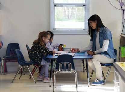 From left, Heidi Wehner, 5, Isabella Galicia, 5, and Nerrys Cancel, lead teacher, are seen from outside the door to Bright Beginnings Learning Center in April.