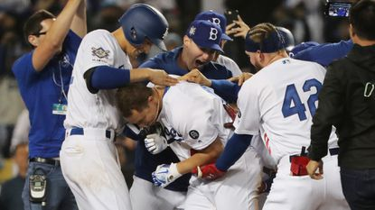 Joc Pederson, center, is mobbed by Dodgers teammates after hitting a walk-off homer to beat the Cincinnati Reds, 4-3, on Monday at Dodger Stadium.