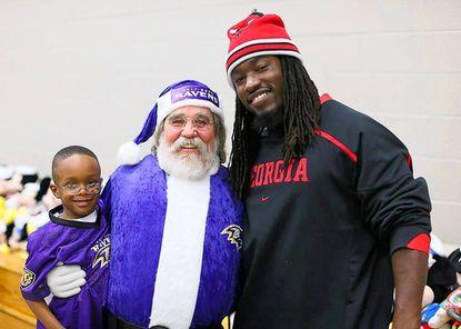 "Bo Fowler dressed as ""Purple Santa."" Standing with him is Raven Dannell Ellerbe. Credit: Bo Fowler."